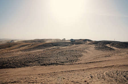 Car overcome sand dunes obstacles. Competition racing challenge desert. Car drives offroad with clouds of dust. Offroad vehicle racing obstacles in wilderness. Endless wilderness. Race in sand desert