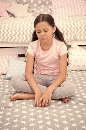 Girl child sit bed bedroom. Kid unhappy someone entered her bedroom bothering her. Girl kid long hair cute pajamas sleepy drowsy unhappy face. Let her sleep longer. Lack of sleep schoolgirl regime Standard-Bild