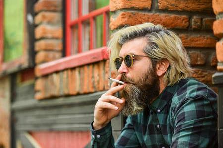 brutal caucasian male in glasses. Man Smoking Outdoor. Fashionable mature man smoking cigarette. Punk hipster man smoking. Smoking and habit. secondhand or passive smoke. copy space Stockfoto