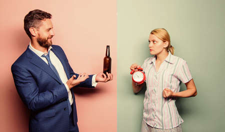want some. man alcoholic drink wine. woman show time on alarm clock. wife wondering why husband reveler came home so late. family routine. problems in relationship. family psychology. unhappy life Stockfoto