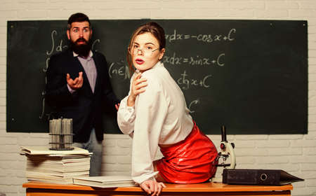 Attractive teacher in leather skirt. Cheeky teacher. Impudent student. Flirting with colleague. Science is sexy. Sexy girl sit table while man stand chalkboard. Everyone dreaming about such teacher
