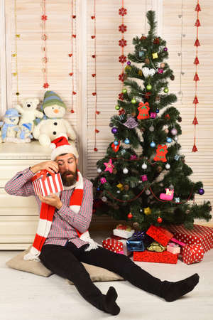 Guy in hat and scarf sits by Christmas tree.