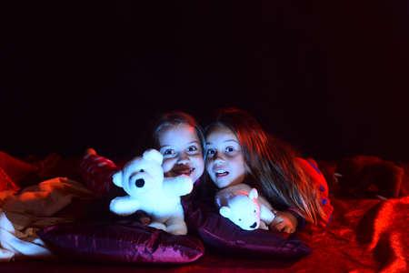 Kids in pajamas lie with teddy bears on dark background.