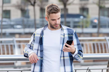 Your true companion. Handsome man use phone outdoors. Online chatting. SMS message. Mobile phone messaging. Cell phone. Smartphone. Portable telephone. New technology. Modern life