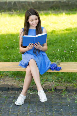 Little happy girl reading book outdoors sunny day, fairy tale concept