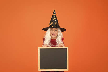 Hi there. have fun. welcome to carnival party. happy halloween. autumn holiday sales. copy space. small girl school blackboard. little witch hat and gray hair. smiling kid info board