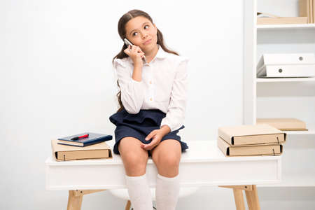 Cute gossip girl. Kid talk with friends. Schoolgirl smiling face discuss fresh gossips with mates. Girl informing parents mark school. Child use smartphone mobile to communicate in school