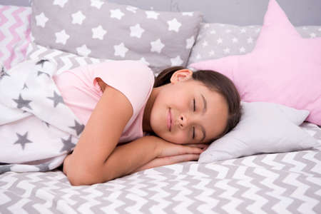 Girl child fall asleep on pillow. Quality of sleep depends on many factors. Choose proper pillow to sleep well. Girl lay on pillow bedclothes background. Child having nap. Cute badclothes and pillows Stock Photo
