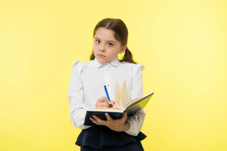 Girl cute schoolgirl in uniform hold book with information yellow background. Pupil get information from book. Child wear school uniform prepare for lesson information. Noticing information