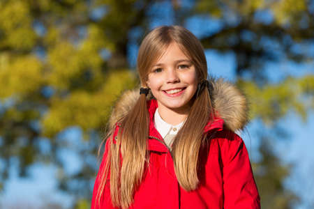 Fall fashion. Kid girl wear coat for fall season. Girl smiling face cute hairstyle fashionable fall coat with hood and fur. Child cheerful walking wearing warm bright coat or jacket fall sunny day