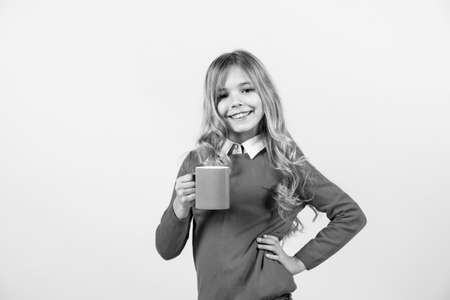 Thirst, dehydration concept. Child smile with blue cup on orange background. Girl with long blond hair in red sweater hold mug. Tea or coffee break. Health and healthy drink Archivio Fotografico