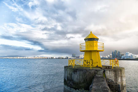Lighthouse on sea pier in reykjavik iceland. Lighthouse yellow bright tower at sea shore. Sea port navigation concept. Sea transportation and navigation. Seascape and skyline with bright lighthouse