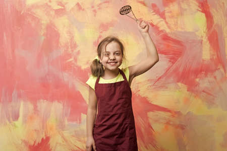 small happy girl chef in cook apron holding cooking tool Archivio Fotografico