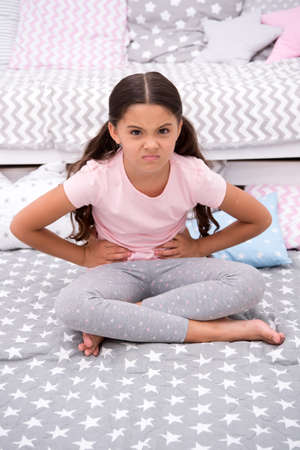 Capricious mood. Girl child sit in bedroom. Kid unhappy capricious someone entered her bedroom bothering . Girl kid long hair cute pajamas capricious face. Let her calm down. How tame capricious kid