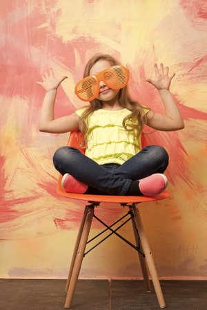 small happy baby girl in orange sunglasses and yellow shirt Archivio Fotografico