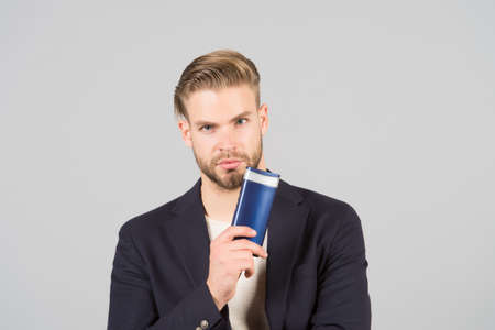 Remedies get rid of dandruff. Man formal suit hold bottle shampoo grey background. Itchy scalp and flakiness skin. Shampoo solve dandruff problem. Dandruff common male problem. Anti dandruff shampoo