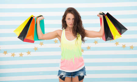 strong shopaholic girl hold shopping bags. beautiful shopaholic. girl holding colorful paper bags in strong hands. power of shopping therapy. this is perfect offer. woman with long hair hold purchase.