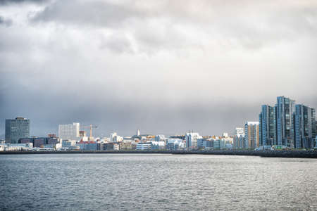 Reykjavik seascape dramatic cloudy sky. City on sea coast Iceland. Scandinavian seascape concept. Calm water surface and city with high buildings modern architecture. Scandinavian city at seashore Archivio Fotografico