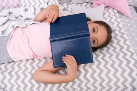 Girl child lay bed read book top view. Kid prepare to go to bed. Pleasant time in cozy bedroom. Girl kid relax and read book. Finished reading and satisfied with happy end. Improve reading skills Archivio Fotografico