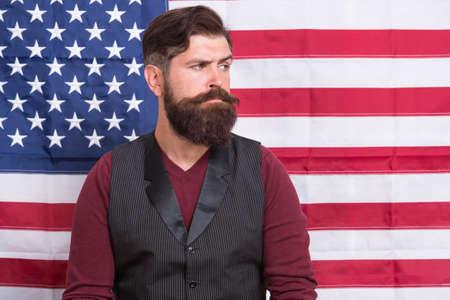 Bearded man migrant apply for citizenship USA flag background, government politics concept Banco de Imagens
