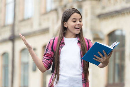 Reading is cool. Happy child read book outdoors. School library. Reading habit. Home reading. Imagination and fantasy. Literacy education. It doesnt take much to make a bookworm happy Stock Photo