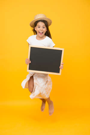 Happy girl child wear summer hat hold chalkboard information copy space, holiday celebration concept