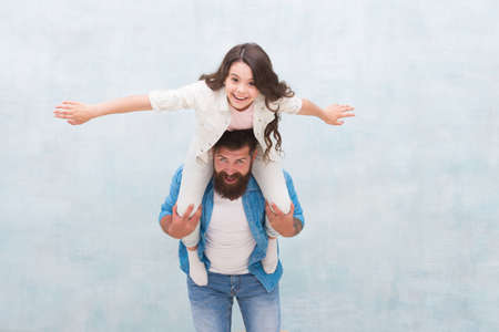 I believe I can fly. Happy father piggyback little daughter. Bearded man and small child play together. Having fun. Active games. Sharing trust relations. Family trust and love. Family values Imagens