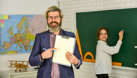 back to school. modern education concept. teacher and child in classroom. change of duties. bearded man make notes in clipboard. little girl write answer on blackboard. exam or lesson. copy space Reklamní fotografie