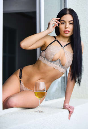 Hot lady erotic lingerie at window sill with wine glass. Reklamní fotografie
