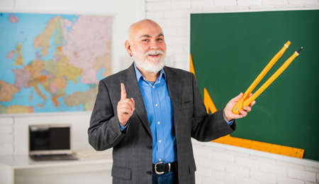 bearded tutor man with compass on blackboard.