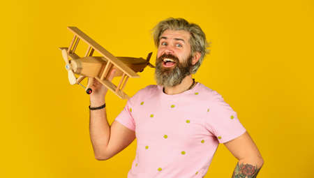 Aviator bearded hipster man holding a Wooden plane toy.