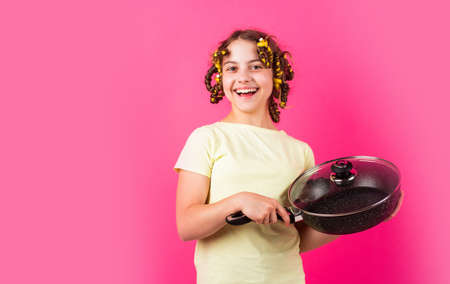Shop home utensils. Kitchen accessories. Culinary and house duties. Stereotype housewife style. Small girl with curlers in hair. Girl hold Frying Pan. Little kid hold pan cooking meal. Pin up style