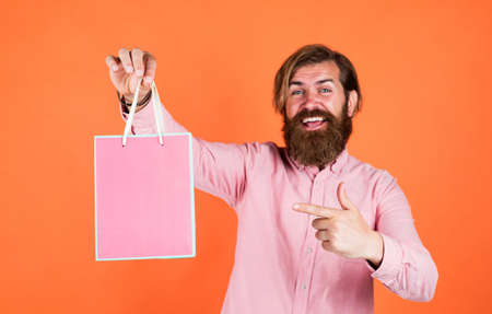 Outgoing man choosing product. happy bearded man with present pack. brutal hipster hold gift. paper shopping bag. birthday surprise at party. man with package. prepare for holidays. best sale offer Stock fotó