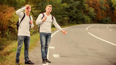 Way of travelling. Just friends and road ahead. feel the freedom. Travelling with friends. Travel by autostop. Hopeless hitchhiker. Men try stop car. twins walking along road. hiker man on road Banco de Imagens