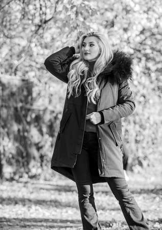Woman long blonde hair wear stylish outfit with parka. Create fall outfit to feel comfortable and pretty. Modern outfit for youth. Girl in warm coat stand in park nature background defocused Stock fotó