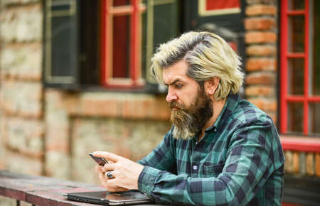 Communication. Send email. Responding message. Urban wifi. Smartphone settings. Application concept. Bearded hipster man hold smartphone building background. Messaging online. Modern smartphone