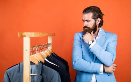 what to choose. Handsome man in smart casual wear looking at suits and choosing. stylish mens clothing on hanger stand in room. business fashion style. dry cleaning service. style and people concept