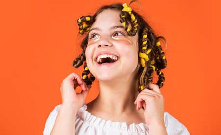Adorable child hairdo. Daughter with curlers on her head laughing. Styling tips. Teen hobbies. Small girl Curling Hair Using Curlers orange background. Hairdresser salon. Female beauty routine