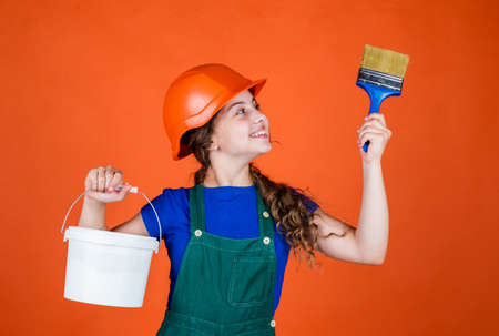 lets start. childhood and people concept. teen kid ready for painting. girl in protective helmet with paint brush. Child care development. Girl in a protective helmet holds the paintbrush Stock fotó