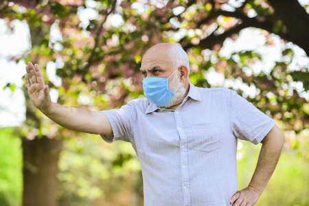 Stop pandemic. Do not touch your face. Support elderly during coronavirus lockdown and social distancing. Senior man wearing face mask. Safety measures. Coronavirus pandemic. Pandemic concept