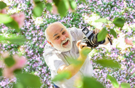 Education for elderly. Vintage camera. Photography hunt. Old happy man looking upwards at tree. Senior man holding professional camera. Retro camera. Photography courses. Grandfather photographer Standard-Bild