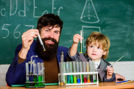 teacher man with little boy. father and son at school. researcher carrying out scientific research in lab. Back to school. lab test tubes and flasks with colored liquids. Listen and You Will See