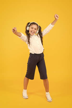 Because Im happy. Happy small girl listening to music on yellow background. Little child enjoying song playing in headphones with smile on happy face. Happy music for kids