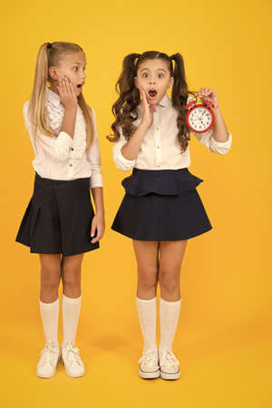School time. Schoolgirls and alarm clock. Children school pupils. Knowledge day. Surprised shocked kids hold alarm clock counting time. Latecomer will be punished. It is time. School schedule