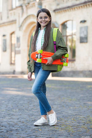 Cruise till you can cruise no more. Happy child hold penny board. Little skater smile outdoors. Riding penny skateboard. Speed and balance. Vacation and holidays. Ride penny board in style