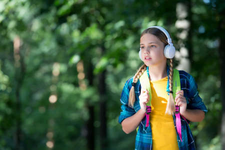 Listening and learning. Small kid listen to music natural outdoors. Listening comprehension. English school. Foreign language courses. Private teaching. Active listening. Summer vacation, copy space