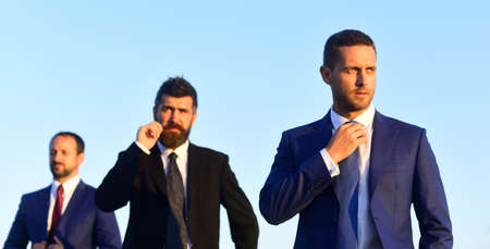 Businessman touches moustache. Men with beard and concentrated faces look
