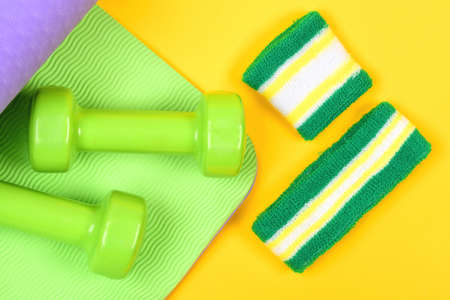 Dumbbells made of plastic on wavy green and yellow background Zdjęcie Seryjne
