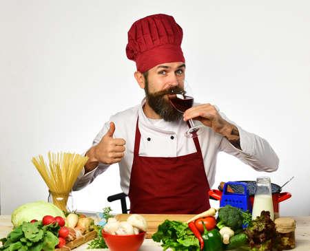 Chef prepares meal. Man with beard drinks wine