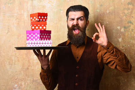 Man with beard holds boxes on beige wall background 스톡 콘텐츠